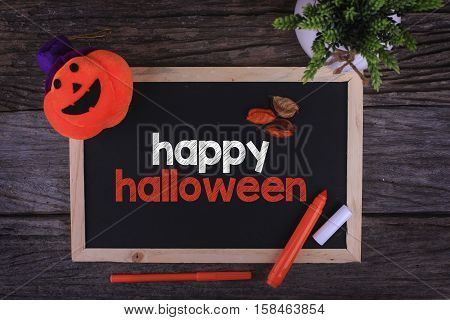Pumpkin Head Candle and a Chalkboard written Happy Halloween on wooden background