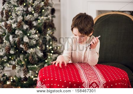 boy calls Santa while sitting on a big green armchair at home over chirstmas tree at background.