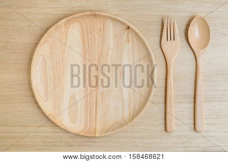 Top view of wooden plate fork spoon on light wooden background