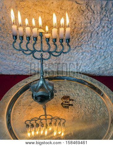 Menorah with the glitter lights of candles and wooden dreidel are traditional Jewish symbols for Hanukkah holiday. Selective focus. Low key image toned for inspiration of retro style and solemn evening ceremony