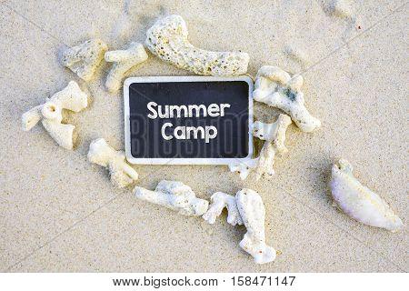 Summer Camp text written on chalkboard on beach