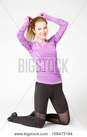 positive smiling athletic girl resting during sports exercises kneeling and straightening hair