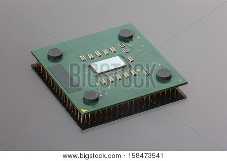 CPU. Modern computer processor unit. The microprocessor is located on a green PCB. 4 mounting pads on the card and microelements around the processor chip. Isolated on gray. Pins reflection.