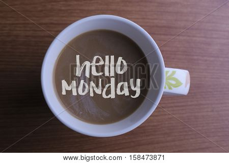 Hello monday./ Inscription hello monday in a cup of coffee and wooden background