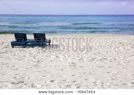 White sandy beach viewing the ocean with empty lounge chairs