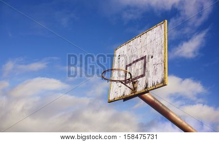 Old wooden basketball board in blue cloudy sky background