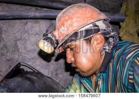 Potosi, Bolivia on September 14, 2015: Portrait of Bolivian miner with helmet and head torch chewing coca leaves while working in Cerro Rico mine