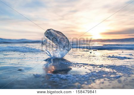 Clear ice floe at frozen surface with reflection and sunset sky. Winter Baikal lake