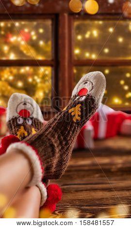 Detail of woman feet in woollen socks, blur Christmas tree on background