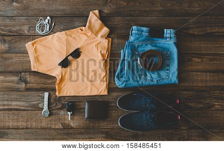 cool fashion men's casual outfit on wooden table, trendy in summer, t-shirt polo, shues, blue jeans pants, sunglasses, watch, wallet and belt, top view