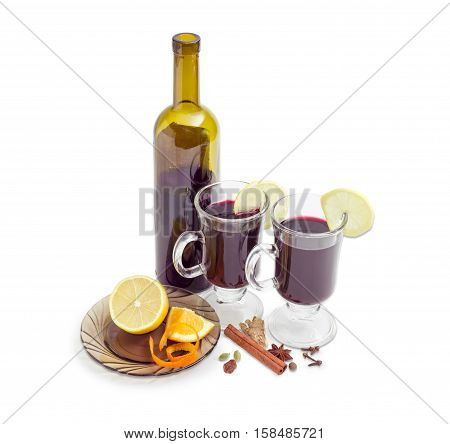 Mulled wine in two glass mugs with slices of lemon bottle of red wine and mulling spices for cooking of mulled wine on a light background