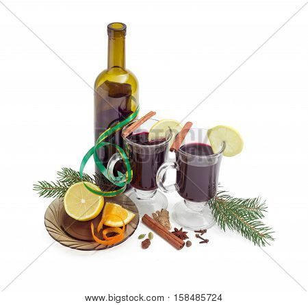 Mulled wine in two glass mugs with slices of lemon bottle of red wine mulling spices for cooking of mulled wine and two fir branches on a light background