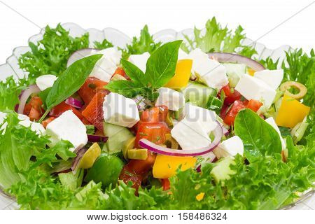 Greek salad decorated with lettuce and basil leaves in a glass salad bowl closeup