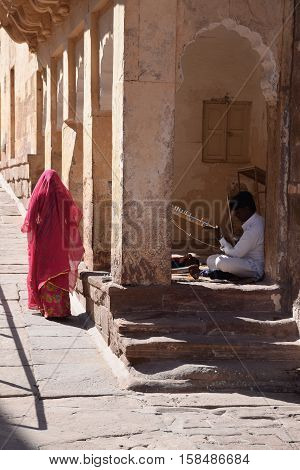 JODHPUR, RAJASTHAN, INDIA - FEBRUARY 10, 2016 - Indian guy playing a traditional instrument inside Mehrangarh fort