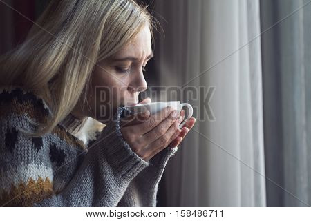 Blonde woman with long hair and warm sweater drinking a cup of hot steamy coffee in the morning by the window