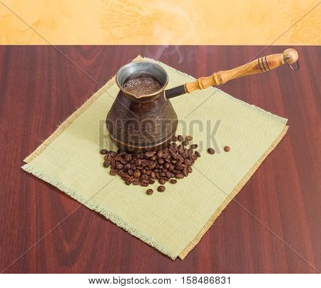 Freshly brewed Turkish coffee in old copper coffee pot and pile of roasted coffee beans on a table mat on a red wooden table