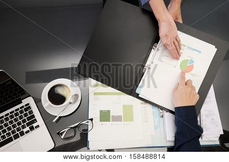 Top view photo of business concept secretary show report to Male manager and point to a business chart it a secretary work vintage tone and soft focus.