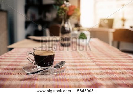 Cup of hot espresso coffee on wood table espresso brew from arabica coffee coffee on Tablecloth in the morning time coffee morning vintage tone.