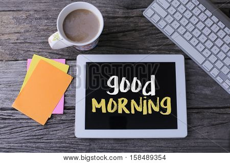 Tablet pc with good morning and a cup of coffee on wooden background