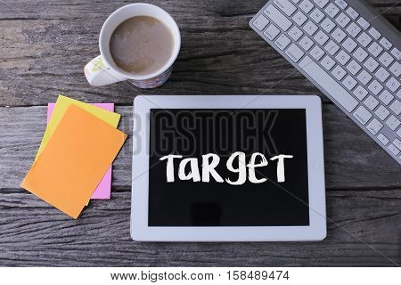 Tablet pc with target and a cup of coffee on wooden background