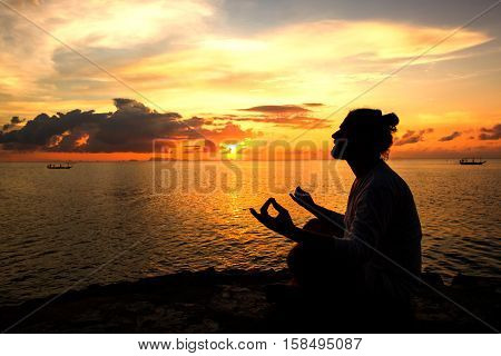Yoga scene man silhouette in sunset background.