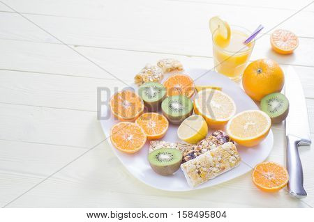 The concept of healthy breakfast orange juice fruit and cereal bars on the wooden table with copy space. Good morning still life. Wonderful breakfast in the bright colors energy boost for the day.