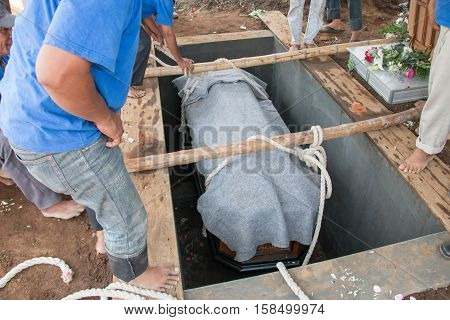 a coffin will be put into the ground to be buried in funeral ceremony
