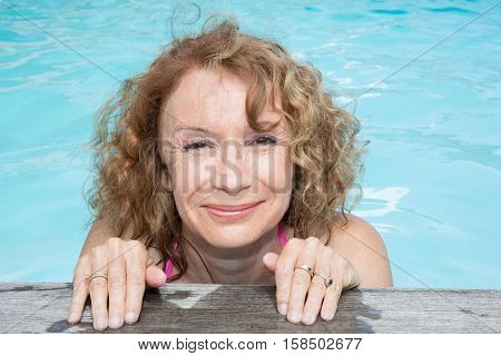 Blond Woman Is Holding The Desck Of Swimming Pool