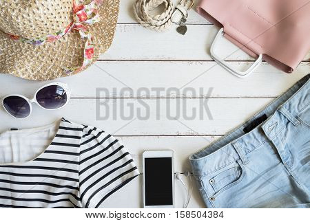 Overhead view of womens cloths accessories and cellphone