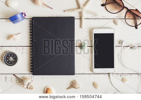 Blank notebook and cellphone with various shell on white wooden background Travel concept
