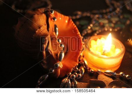 real big shell from sea decorated silver chain and bright burn candle adorn for holiday night