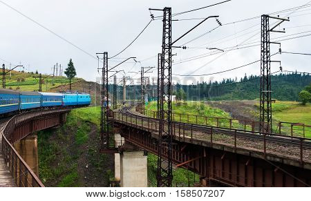 Passenger train going across the bridge in the Carpathian Mountains