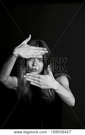 The girl with long hair holding his hands in front of my eyes for the frame. Black and white, Studio
