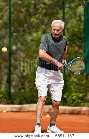 Senior man on tennis court, toned image, outdoors
