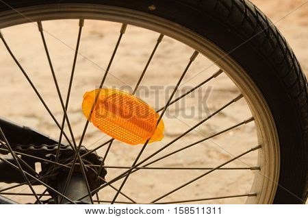 Close up of a bicycle wheel showing the orange reflector and spokes