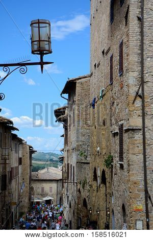 San Gimignano Italy - September 6 2016: Buildings and street in San Gimignano city in Tuscany Italy. Unidentified people visible.