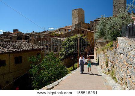 San Gimignano Italy - September 6 2016: Narrow street in San Gimignano city in Tuscany Italy. Unidentified people visible.