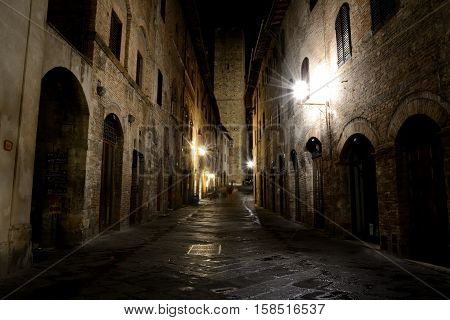 San Gimignano Italy - September 6 2016: Street at night in San Gimignano city in Tuscany Italy. Unidentified people visible.