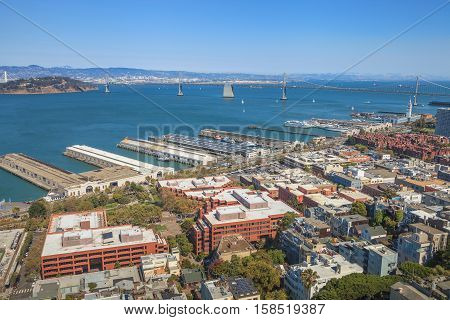 Aerial panorama of San Francisco North Beach, Embarcadero and Oakland Bridge, from top of Coit Tower on sunny day. Telegraph Hill, California, United States.
