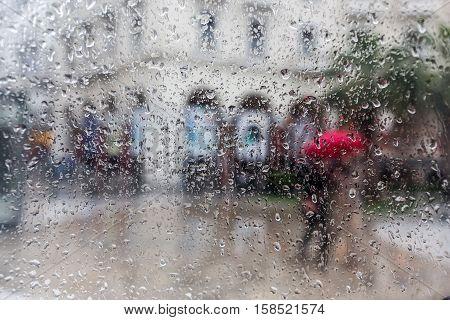 Raindrops On A Window Pane. Blur People In The Rain.