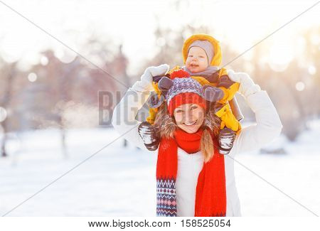 happy family mother and baby is happy the snow on a winter nature walk