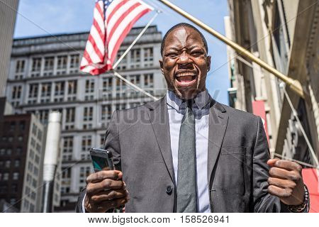 Afromerican businessman exulting outdoors, triumphant man in New York