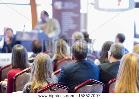Male Host Speaking in Front of the Audience Against White Screen.Horizontal Shot