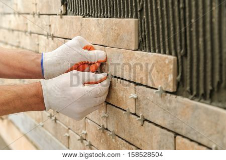 Installing the tiles on the wall. A worker putting tiles in the form of brick. He places the plastic crosses between the tiles.