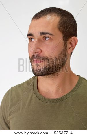 A young unshaven handsome man looking faraway