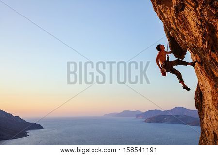Rock climber resting while climbing overhanging cliff