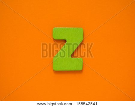 Capital letter Z. Green letter Z from wood on orange background.