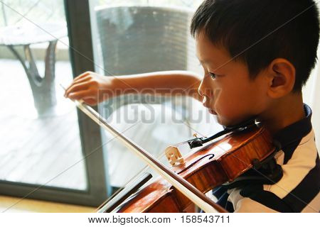 teenager asian boy playing the violin