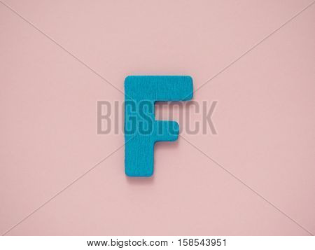 Capital letter F. Blue letter F from wood on pink background.