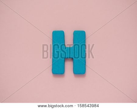 Capital letter H. Blue letter H from wood on pink background.